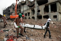 Rescuers carry a body retrieved from the rubble of the eight-story Rana Plaza building that collapsed in Savar, near Dhaka, Thursday, May 9, 2013. The death toll from the collapse of the garment factory building passed 900 on Thursday even as a fire in an 11-story garment factory Wednesday night in Dhaka killed eight people, including a ruling-party politician and a top official in the country's powerful clothing manufacturers' trade group. (AP Photo/Ismail Ferdous)